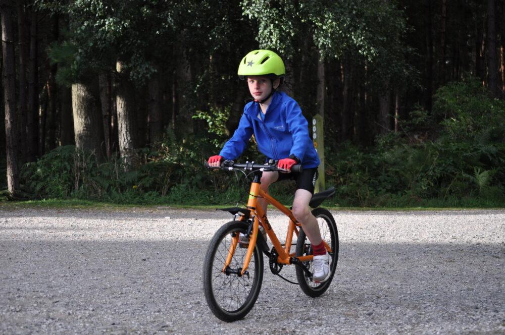 best bike for my child - boy on orange Frog 55 hybrid bike