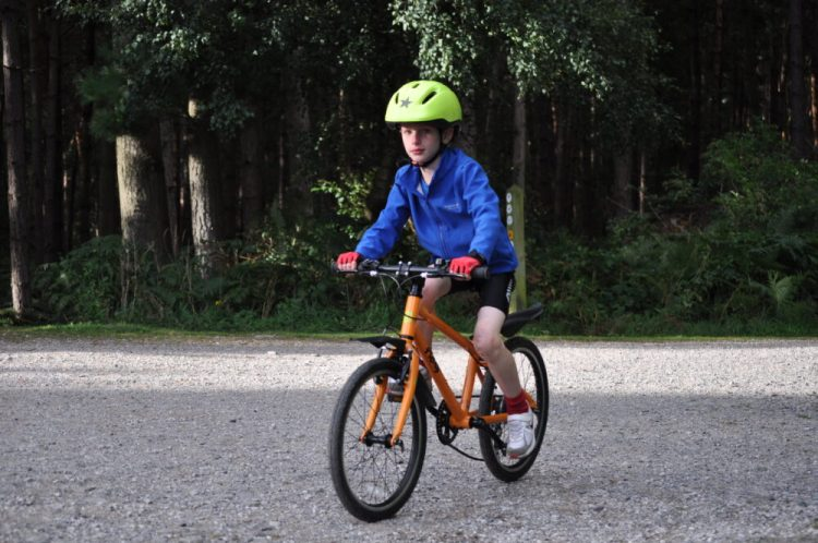best bike for my child - boy on orange Frog 55 hybrid bike