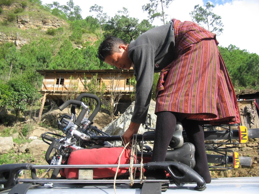 driver Namgay loading bikes on top of car