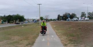 in lange broek en regenjack over het vrijliggende fietspad de stad uit.