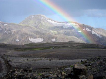 Regnbåge på Island. Berg och kargt.