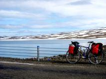 Snö och is vid sjö med långfärdscykel