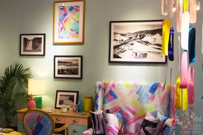 colorful settee, chandelier, framed photos and art