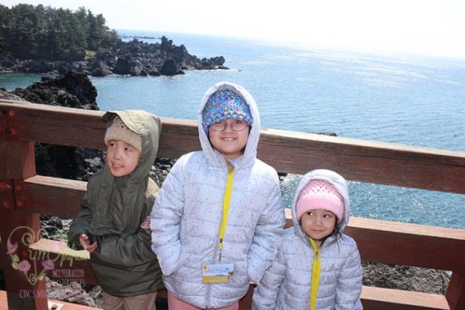 kids on jeju island cliffside