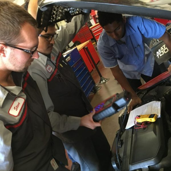 students working in the automotive technology program to repair a car