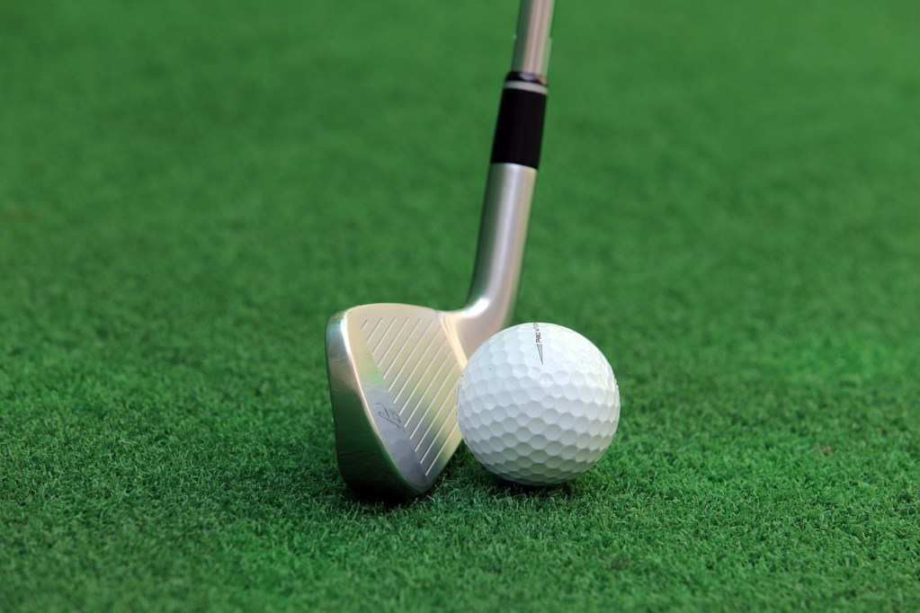Golf club and ball on grass
