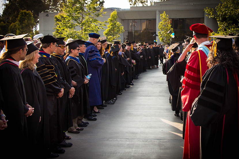 Faculty and Administration in commencement regalia standing to form a pathway for students to walk through