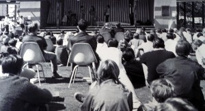 Students watching a performance on an outdoor stage