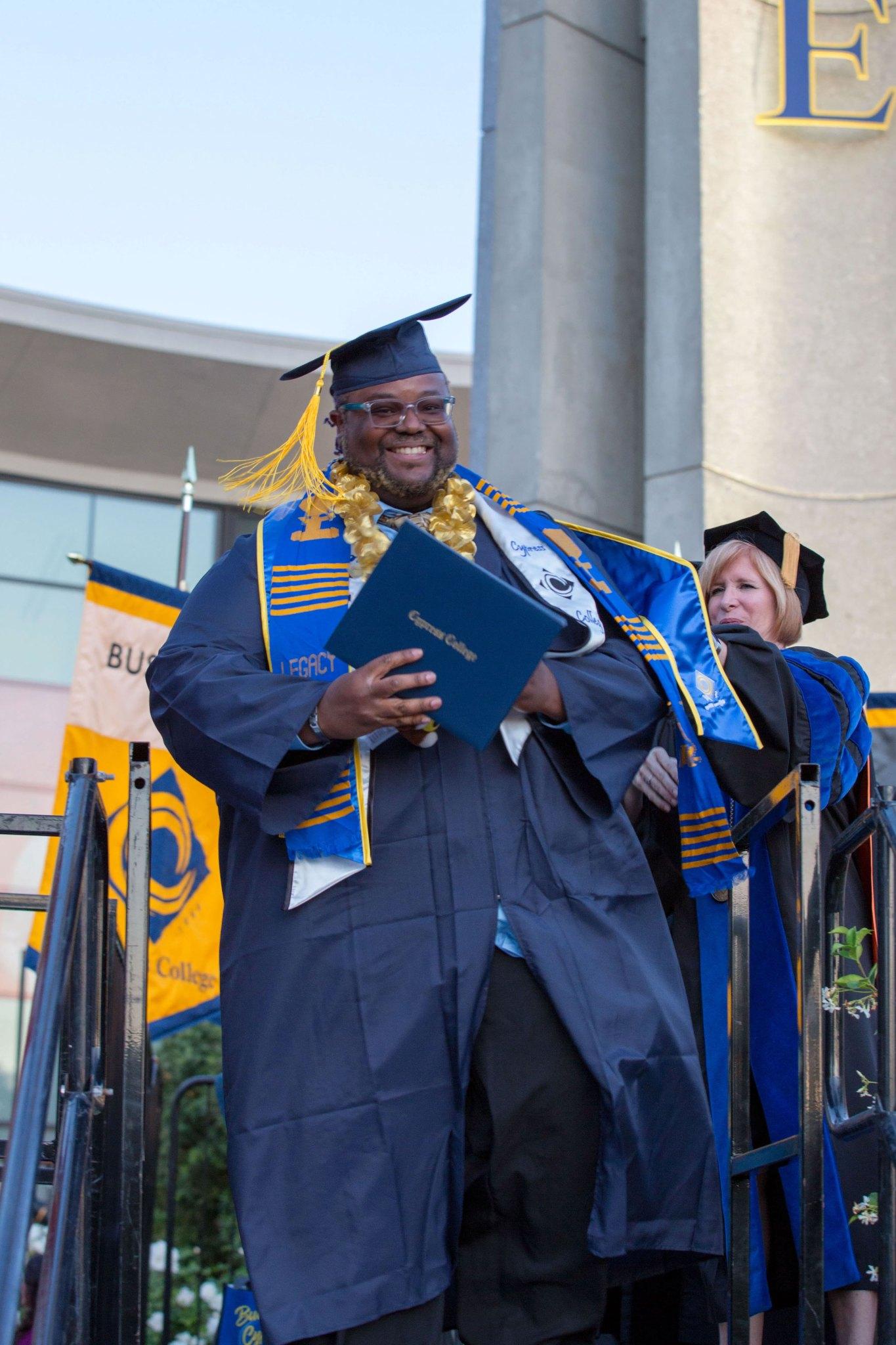 Student graduating, holding diploma