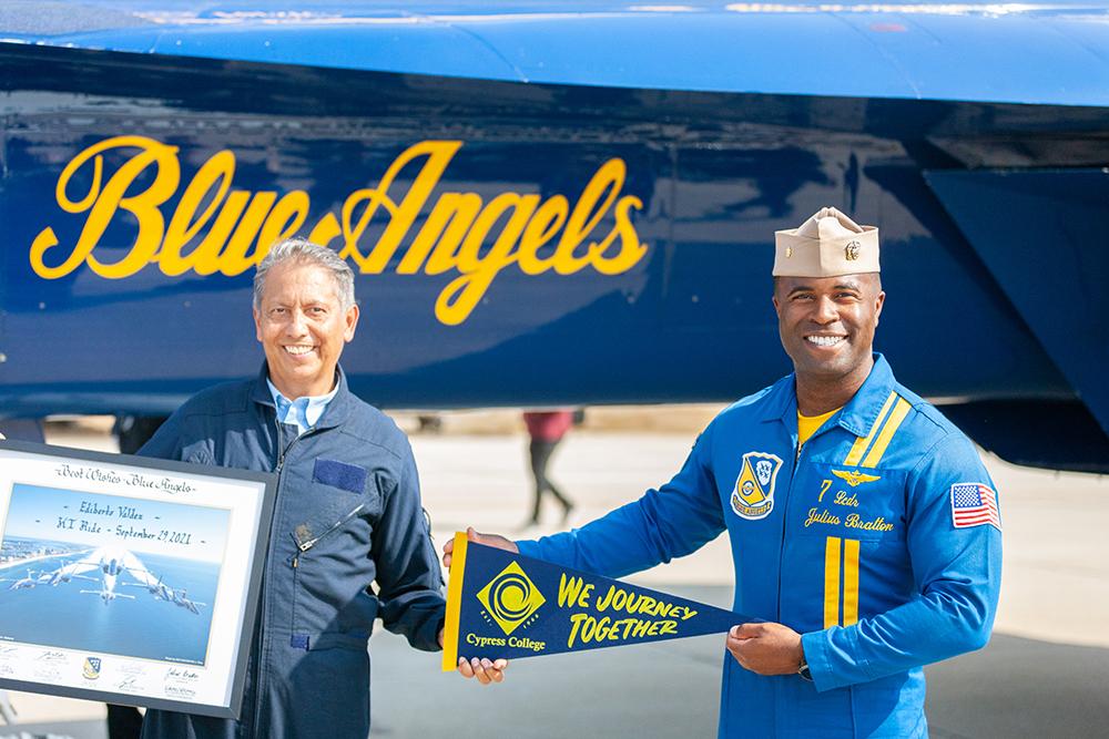 Ed Valdez holds a banner with Blue Angels pilot Justin Bratton.