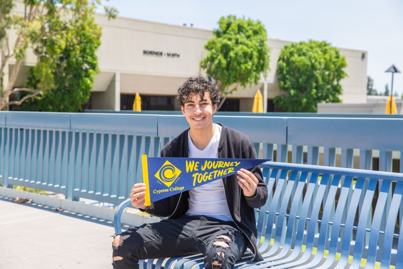 Student Nader Barsoum holding a pennant and sitting on a bench on campus