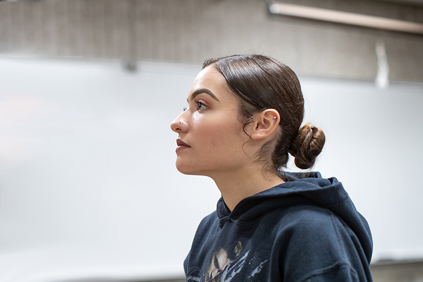 Female student wearing a sweatshirt gazing in front of her