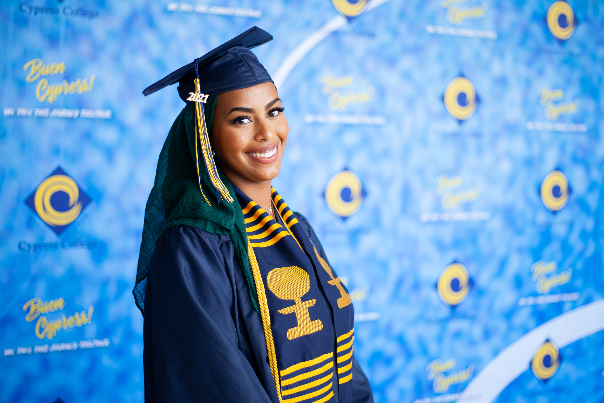 Counseling student Ayah Said poses in front of blue background with Legacy Program sash.