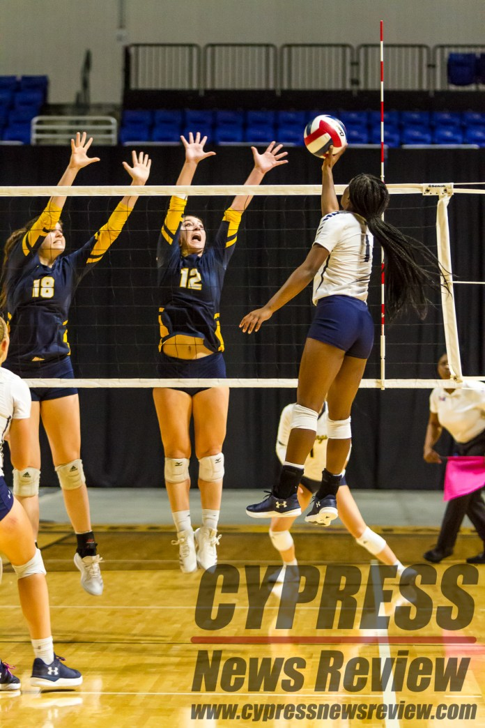 Karli Rose (Tomball Memorial #1) attacks against the double block of Elayne Grisbee (Cy Ranch #18) and Peyton DeBello (Cy Ranch #12) during the intra-district playoff, and the effective district championship at the Berry Center Oct. 26, 2018. Both Rose and DeBello earned honorable mention spots on the Texas Sports Writers Association's 2018 All-State team. (Cypress News Review photo by Creighton Holub)