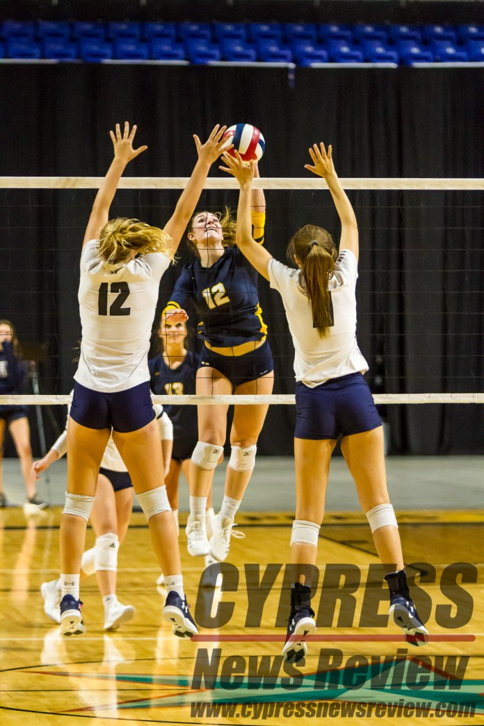 Peyton DeBello (Cy Ranch #12) spikes the volleyball against a flying double block during the intra-district playoff, and the effective district championship at the Berry Center Oct. 26, 2018. DeBello earned a honorable mention spot on the Texas Sports Writers Association's 2018 All-State team. (Cypress News Review photo by Creighton Holub)