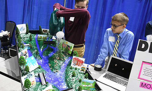Spillane Middle School seventh-grader students Connor Kaminski (pouring water) and Tristan Huffman showcase their project, which replicates a watershed and its water flow, at the CFISD Horizons Student Showcase on Jan. 28, 2019, at the Berry Center (CFISD courtesy photo)