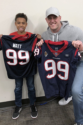Houston Texans star JJ Watt (right) poses with Moore Elementary School fourth-grade student Brock Givens with two football jerseys on Feb. 13 after responding to a post on Twitter showing Givens wearing a makeshift version of Watt's No. 99 jersey. Givens' teacher, Malinda Ross, asked her students to join her in wearing the jerseys to recognize the 99th day of the school year. Watt personally delivered the two jerseys to Givens. (CFISD courtesy photo)