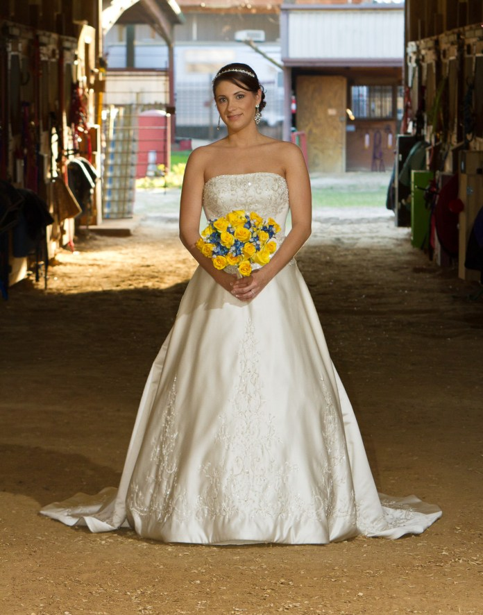 A bride enjoys the country esthetic at Oak Hollow Equestrian Center in Cypress, Texas. Visit their website at https://www.oakhollowec.us/ (courtesy photo from Holub Photography)