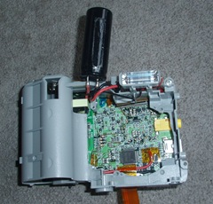 The lens removed and capacitor lifted on an Olympus D-535.