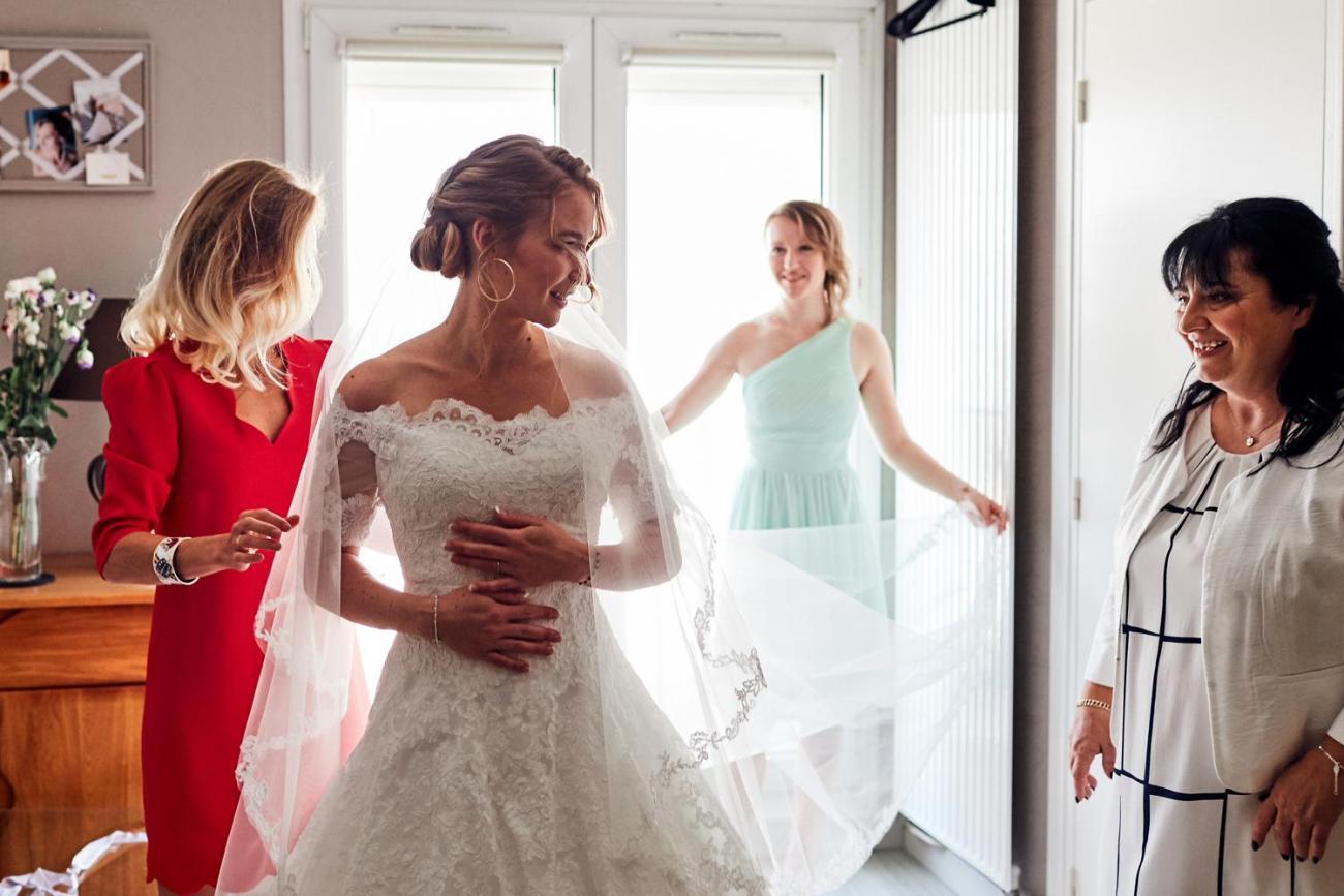 La mariée enfile sa robe