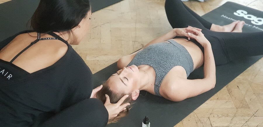 Fotografija žene koja prakticira yogu uz asistenciju trenerice