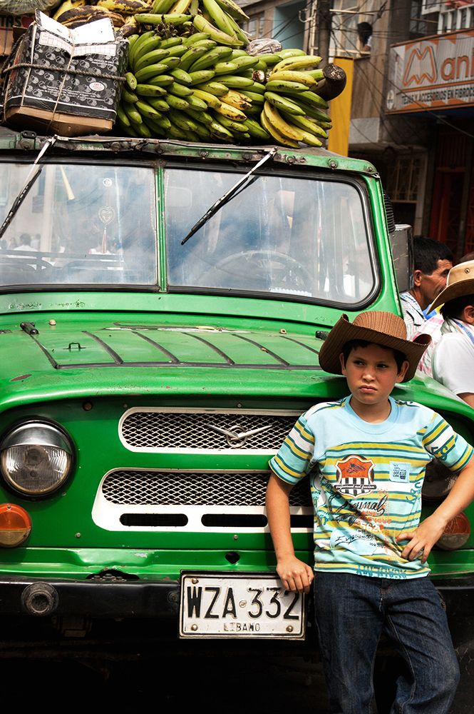 Color photo of a boy wearing a staw hat standing in front of a green jeep with plantains on top.