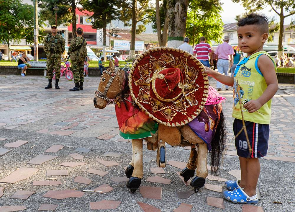 Color photo of a latino boy with a toy riding horse with police in background.