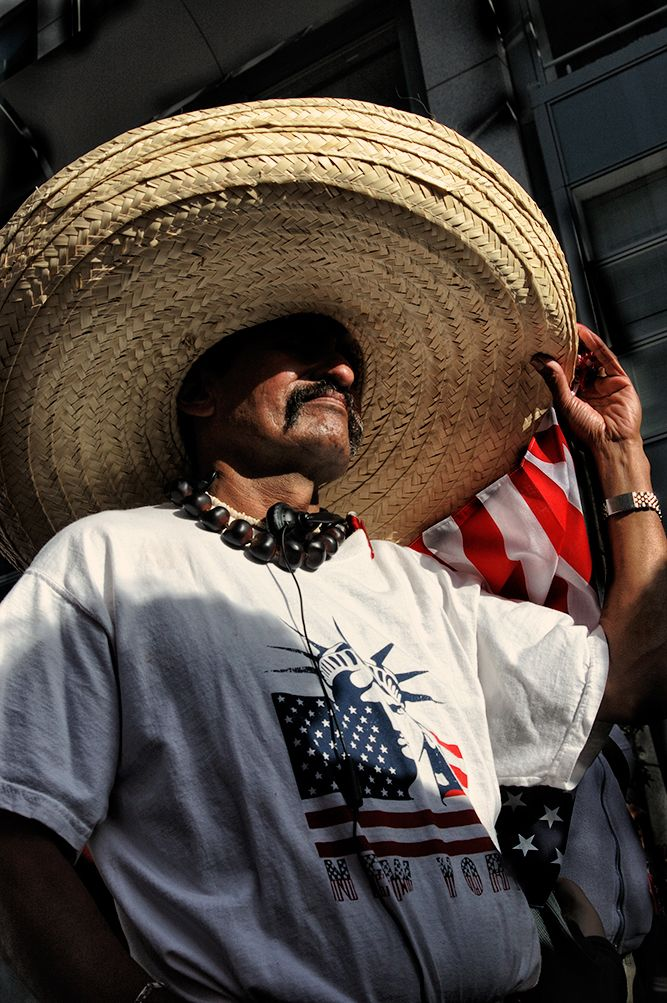 Color photo of a latino man wearing a huge Mexican sombrero.