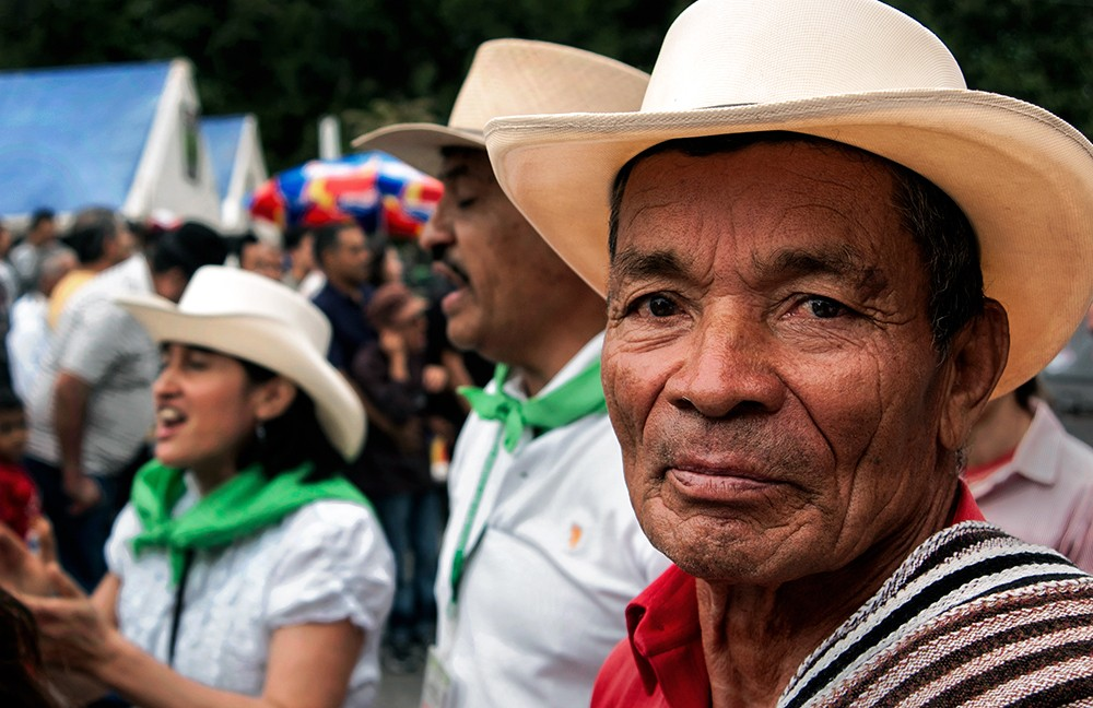Color photo of Colombian man wearing a straw hat and poncho.