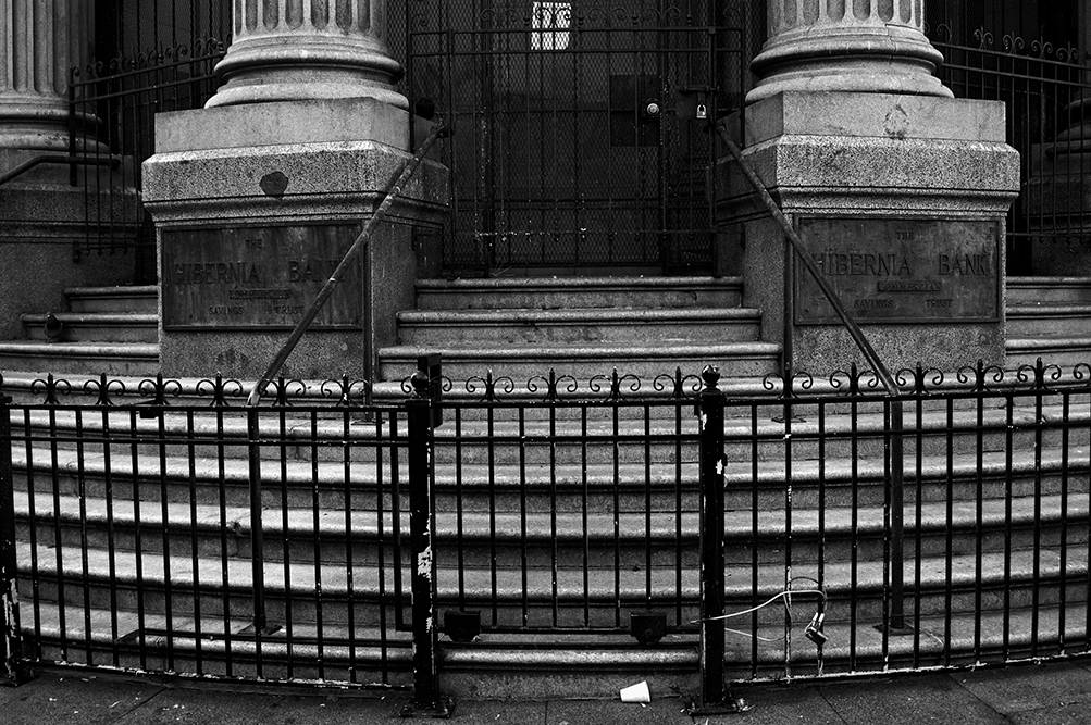 Black and white photograph of an iron gate in front of a set of steps leading to stone columns.