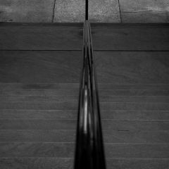 Semi-abstract black and white photograph looking down an iron rail toward the sidewalk.