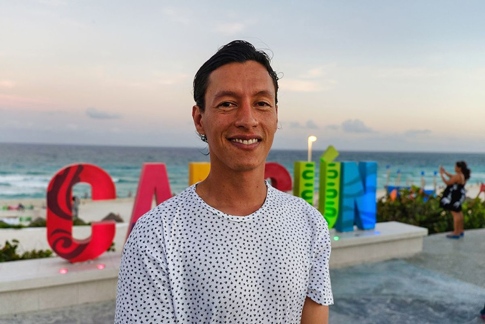 Color photo of a latino at the beach in Cancun at sunset with a Cancun sign in the background.