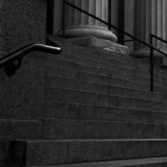 Black and white photograph looking up a set of steps leading to stone columns.