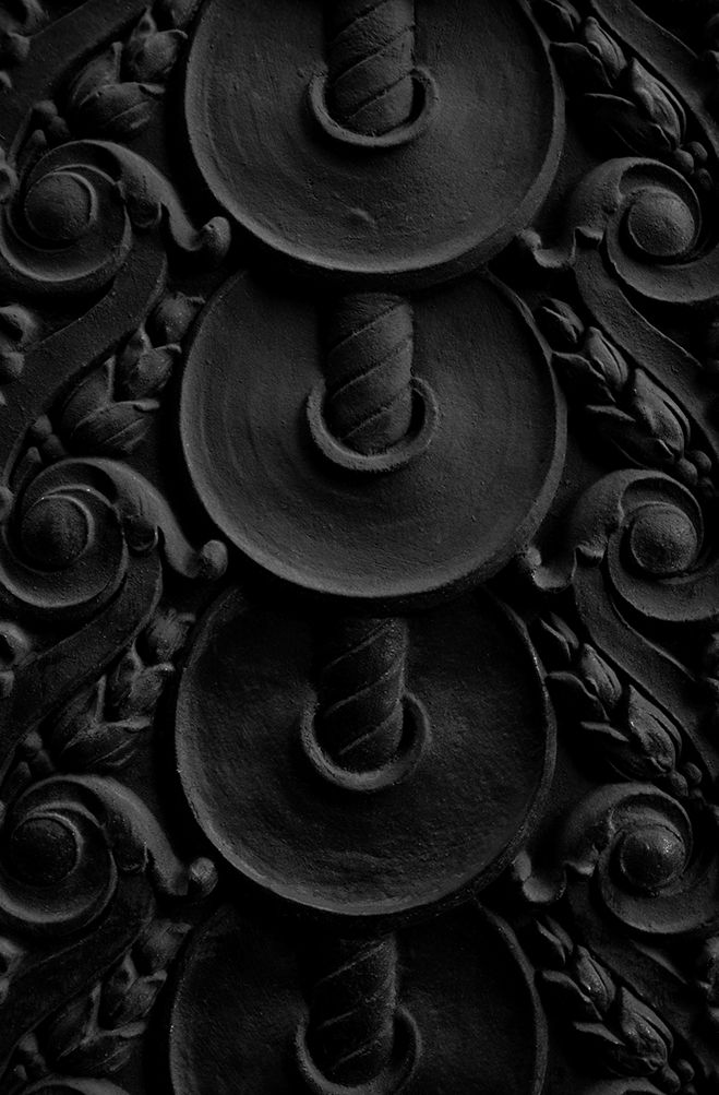 Black and white photograph of ornate iron detail on the side of a building.