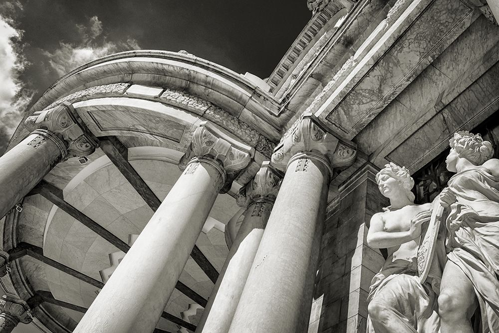 Black and white photo of statues and columns at the entrance of a building.