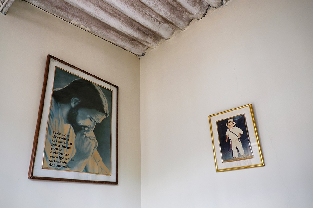 A color photo of two pictures hanging on a wall, one of Jesus and the other of a small boy wearing traditional white Colombian clothes.
