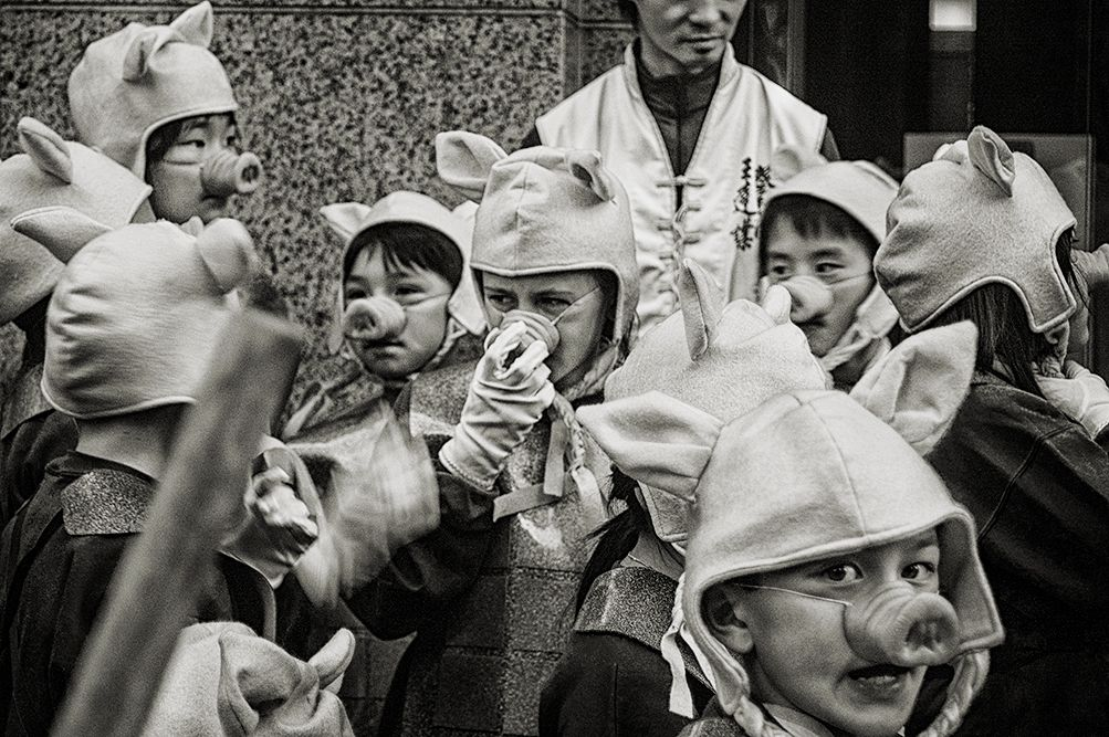 Black and white photo of Asian children dressed as pig to celebrate the Chinese New Year.