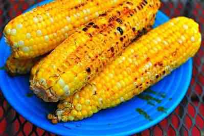 Grilled corn stacked on a blue plate