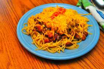 A plate of five way - spaghetti, chili, beans, onions and cheese