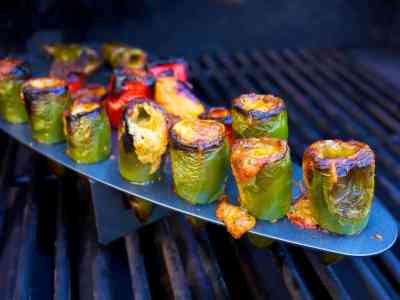 Jalapeno peppers stuffed with melted cheese in a rack on a grill