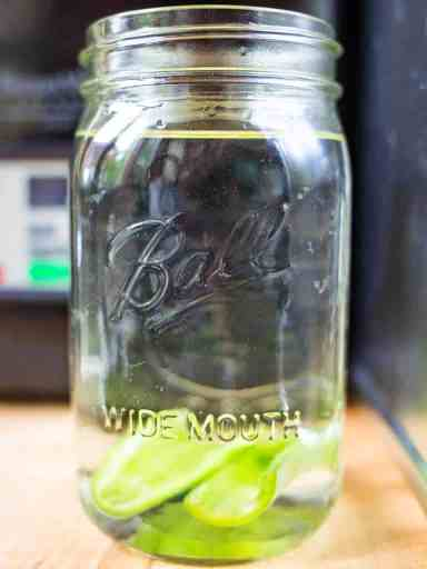 Canning jar full of tequila with sliced jalapeno pepper wedges sunk to the bottom