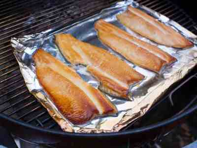 Smoked trout on a piece of aluminum foil in a grill