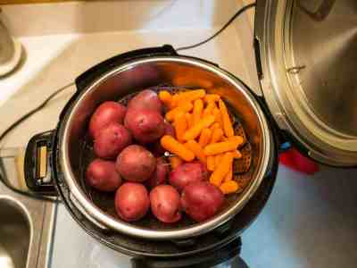 Potatoes and carrots in a basket on top