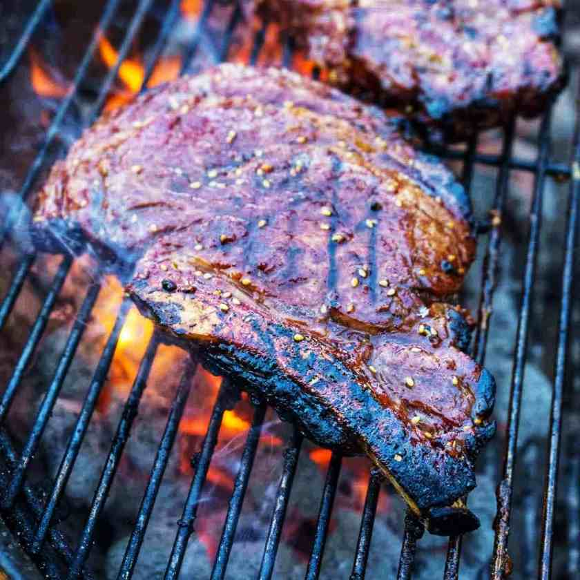 Ribeye steak on a grill, over charcoal, with a flare of fire and a second ribeye in the background