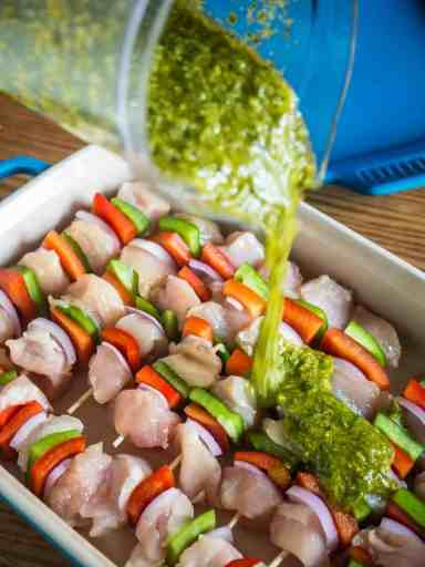 Pouring salsa verde onto the kebabs - Grilled Chicken Kebabs With Italian Salsa Verde | DadCooksDinner.com