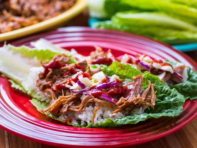 Lettuce wraps with shredded Korean pork, kimchi, and white rice on a red plate, with a plate of lettuce leaves in the background.
