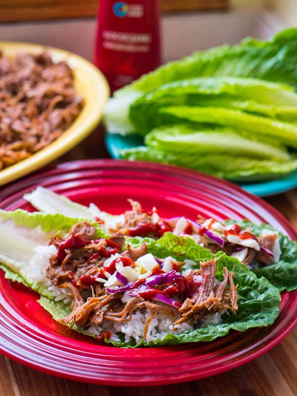 Lettuce wraps with shredded Korean pork, kimchi, and white rice on a red plate, with a plate of lettuce leaves and a bottle of gochujang in the background.