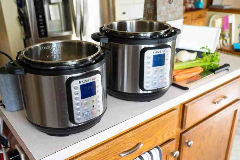 Two pressure cookers with vegetables on a cutting board