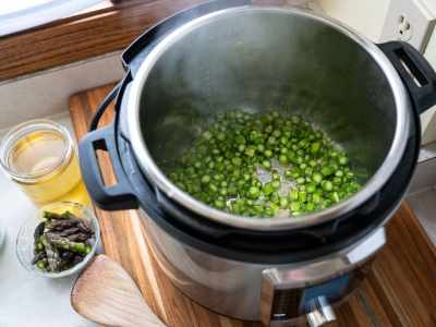 Instant pot sauteing cooking shallots and asparagus stalks, with a jar of broth and a small bowl of asparagus tips on the side