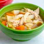 A green bowl full of chicken noodle soup